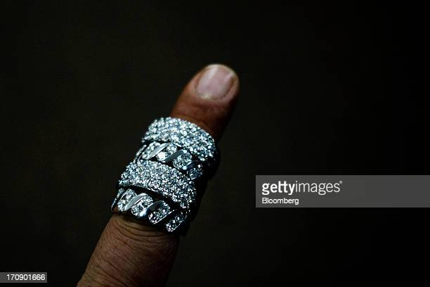 A worker displays Kama Schachter Jewelry Pvt Ltd rings for a photograph at the company's diamond studded gold and platinum manufacturing facility in...