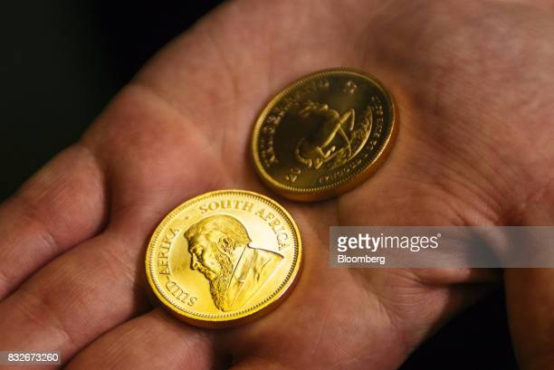 A worker displays the front and reverse sides of proofed gold krugerrand coins at the Rand Refinery Ltd plant in Germiston South Africa on Wednesday...