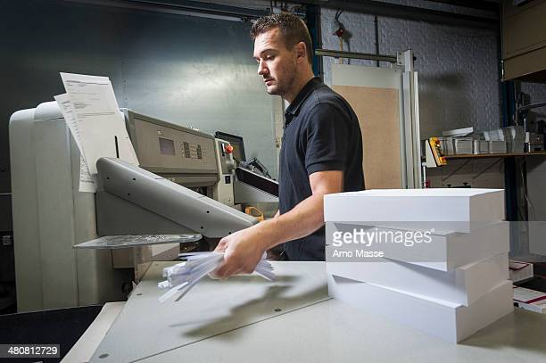 Worker disposing of paper trimmings in print workshop