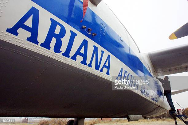 A worker does maintenance on an Ariana Afghan Airlines plane on the tarmac at the Kabul airport January 10 2002 in Kabul Afghanistan The airport is...