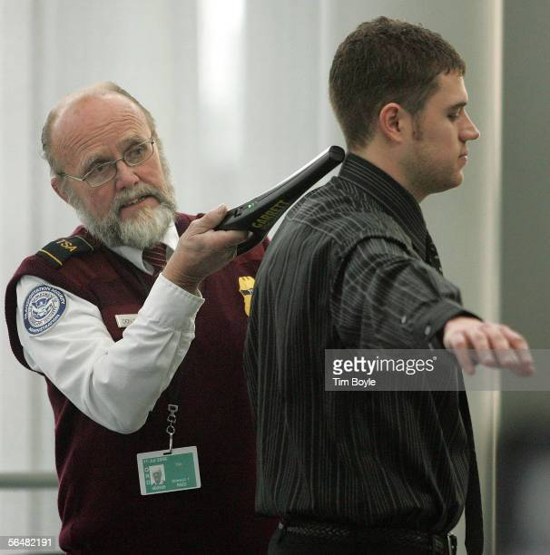 TSA worker Donald Reid checks a traveler at a security post at O'Hare International Airport December 22 2005 in Chicago Illinois According to the TSA...