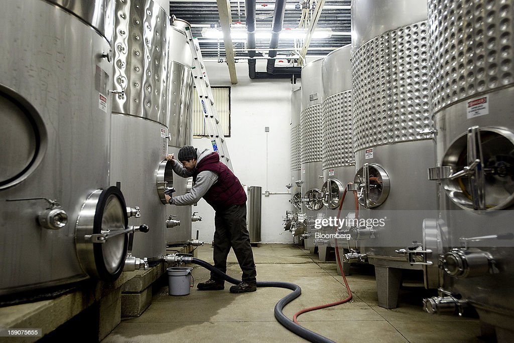 A worker drains one of the fermenting tanks at the Ferrante Winery in Geneva, Ohio, U.S., on Friday, Jan. 4, 2013. Ice wine is a type of dessert wine produced from grapes that have been frozen while still on the vine, because the sugars and other dissolved solids do not freeze, but the water does, this allows a more concentrated grape must to be pressed. Photographer: Ty Wright/Bloomberg via Getty Images