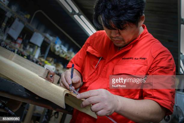 Worker drawing to wood interior part at mohenic garages in Paju South Korea A 20yearold beat up Hyundai SUV isn't anyone's idea of a dream car But...
