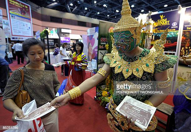 A worker dresed in Thaia traditional costume distributes leaflets during the tourism promotion in Bangkok on March 5 2009 Thai cabinet approved a 5...