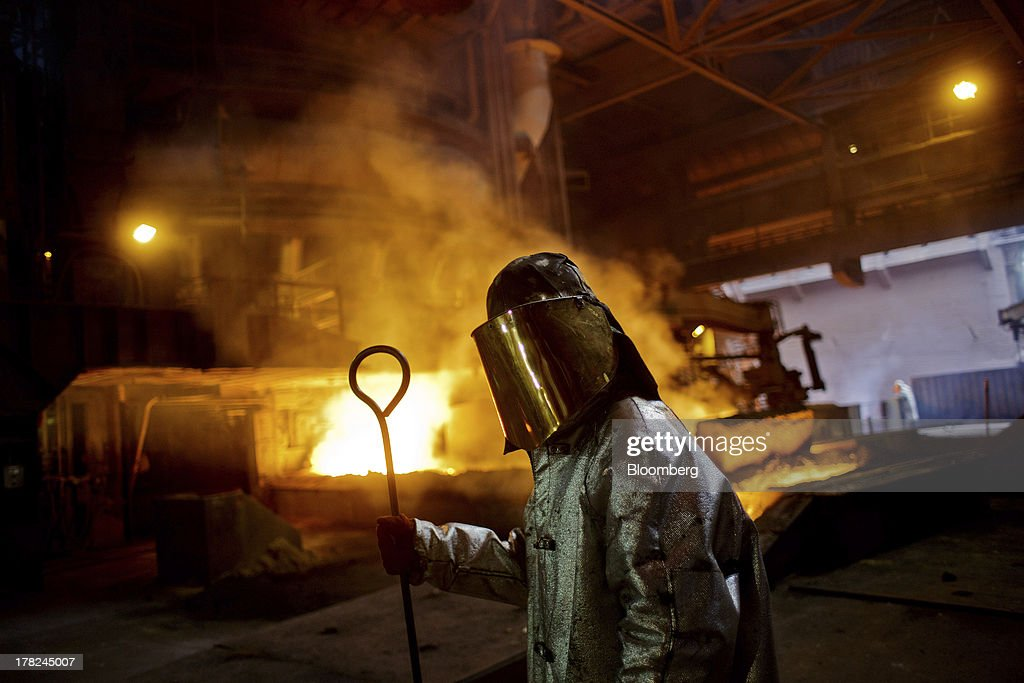 A worker dressed in heat retardant safety clothing pauses while working near the blast furnace at ArcelorMittal's steel plant in Ostrava, Czech Republic, on Monday, Aug. 26, 2013. ArcelorMittal, the world's biggest steelmaker, said steel shipments will rise 1 percent to 2 percent this year compared with an earlier forecast of 2 percent in May. Photographer: Martin Divisek/Bloomberg via Getty Images