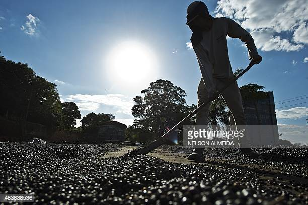 A worker dries organic coffee beans produced at the Fortaleza Environmental Farm in Mococa some 300 km northeast of Sao Paulo Brazil on August 6 2015...