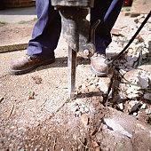 Worker drilling ground