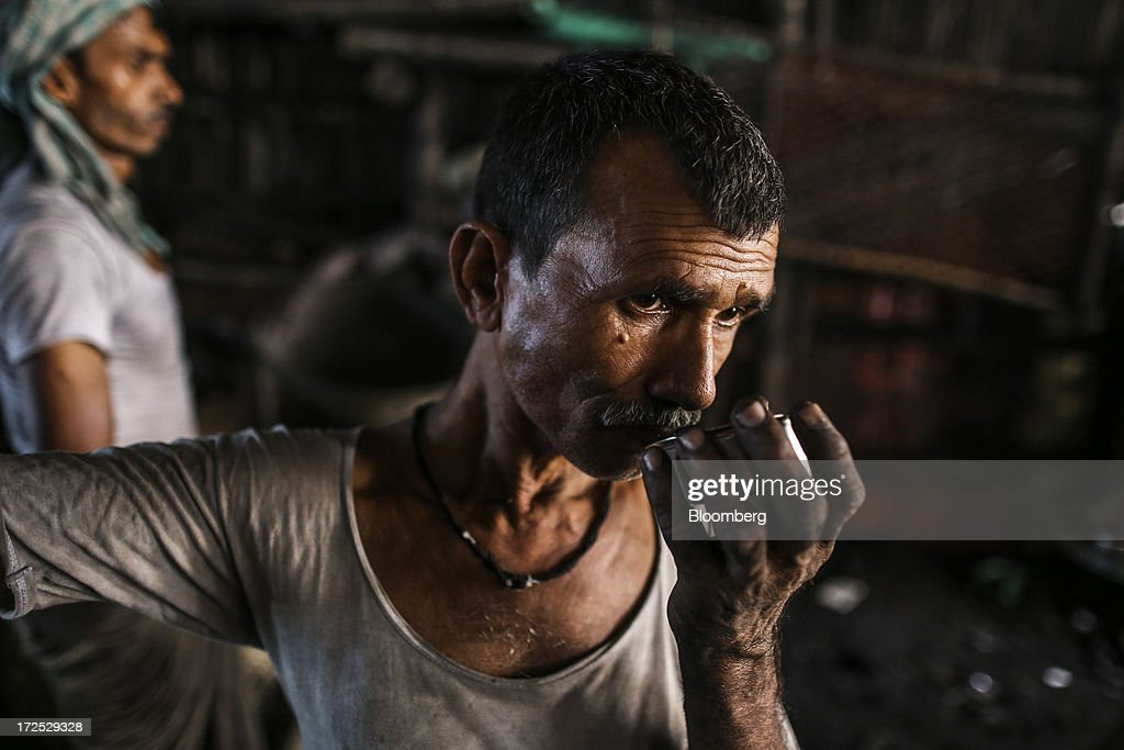 A worker drinks tea during a break at a coal wholesale market in Mumbai, India, on Tuesday, July 2, 2013. India, the worlds third-largest coal consumer, imported 43 percent more of the fuel than a year ago on increased demand from power stations and steelmakers, according to shipping data, and is set to eclipse China as the top importer of power station coal by 2014. Photographer: Dhiraj Singh/Bloomberg via Getty Images