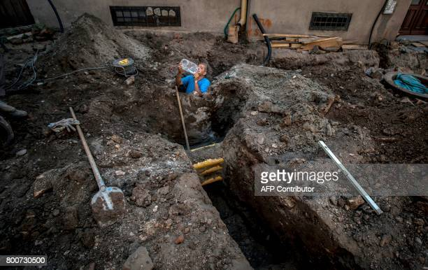 A worker drinks water at a construction site in the center of the Serbian capital Belgrade on June 25 2017 as a heat wave sweeps the country with...