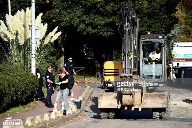 A worker drives a backhoe as police stand guard near the area where an incendiary device was thrown and exploded on a construction site near the...