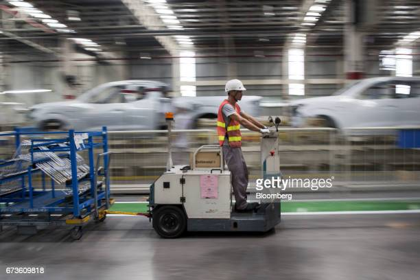 A worker drives a cart pulling a trailer loaded with components for Nissan Motor Co Navara pickup trucks through the company's plant in Samut Prakan...