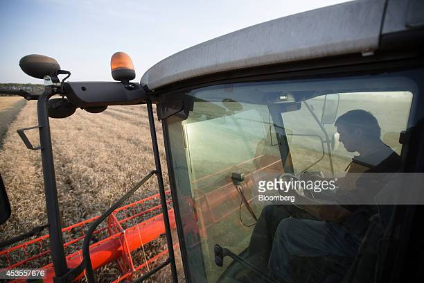 A worker drives a Claas KGaA combine harvester across a wheat field during the summer harvest on the OOO Barmino farm enterprise in Vargany near...