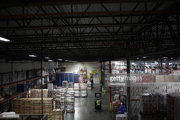 A worker drives a forklift past stacks of wine and spirits in the distribution warehouse at Southern Wine and Spirits Inc in Louisville Kentucky US...