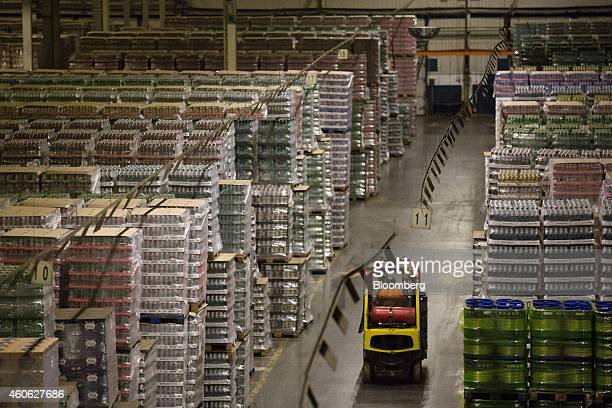 A worker drives a forklift truck past stacked pallets of beer in the distribution center at the OAO Baltika brewery operated by Carlsberg A/S in...