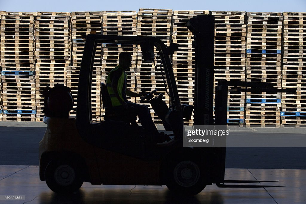 A worker drives a fork-lift truck past stacked wooden pallets in an outside storage area at the Lanitis Bros Ltd. bottling plant, part of the Coca-Cola Hellenic Group, in Nicosia, Cyprus, on Tuesday, June 10, 2014. Zug, Switzerland-based Coca-Cola Hellenic Bottling Co., which distributes Coca-Cola products in countries including Russia, wants to move away from using imported sugar for its Russian operations by 2015. Photographer: Andrew Caballero-Reynolds/Bloomberg via Getty Images