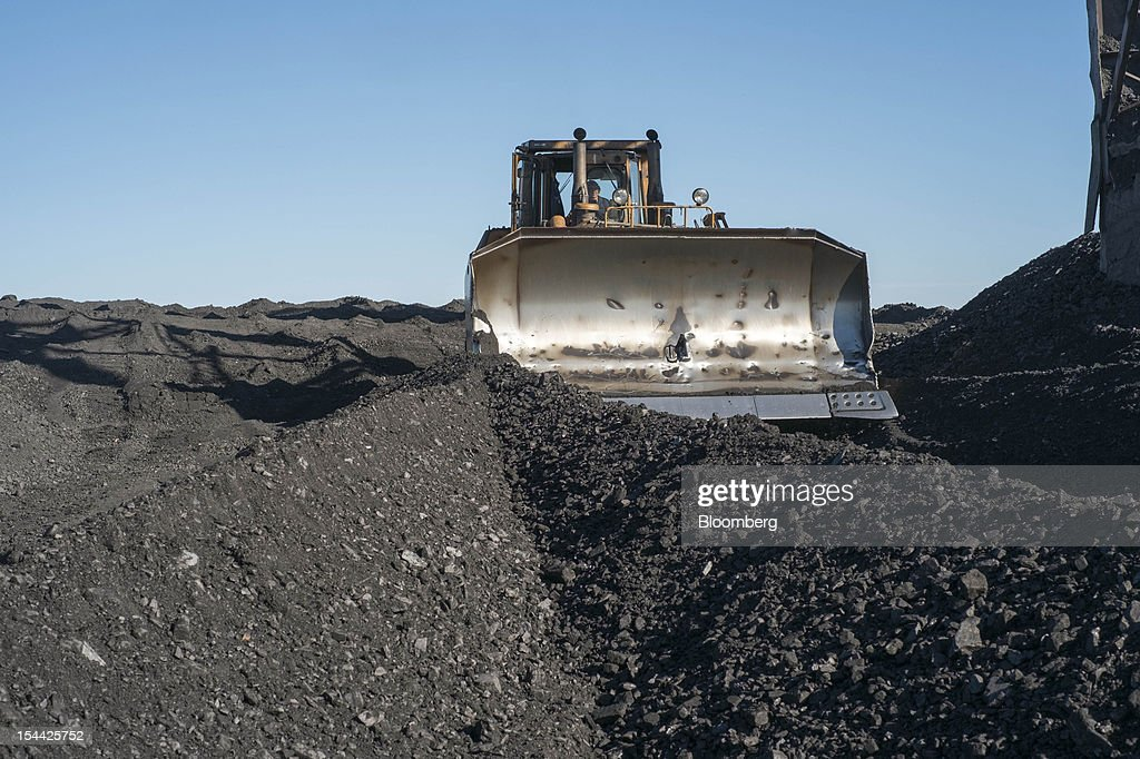 A worker drives a front-loader bulldozer to move coal around a storage area at the Vostok Energo power plant, operated by the Donbass Fuel & Energy Co., or DTEK, in Donetsk, Ukraine, on Thursday, Oct. 18, 2012. DTEK, Ukraine's largest private coal and energy producer, signed a supply contract with OAO OGK-2, the Russian wholesale power generator controlled by OAO Gazprom. Photographer: Vincent Mundy/Bloomberg via Getty Images