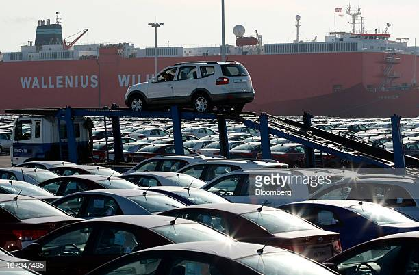 A worker drives an SUV bound for export off of a truck at the port in Pyeongtaek South Korea on Monday Dec 6 2010 South Korea said the revised free...