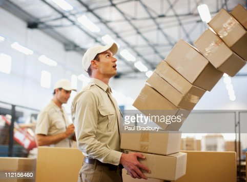Worker dropping boxes in shipping area : ストックフォト