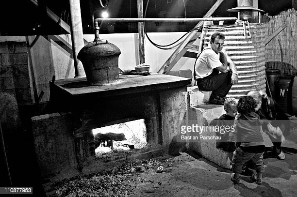 A worker during a raki production take a break and watching the playing children at the distillery on October 23 2009 in Heraklion Greece Raki is a...