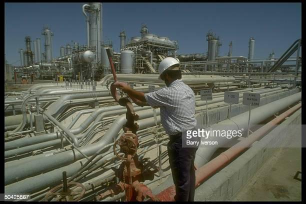 Worker dwarfed by sprawling network of pipelines storage tanks at Saudi Aramco oil refinery loading terminal at Ras Tanura Arabia