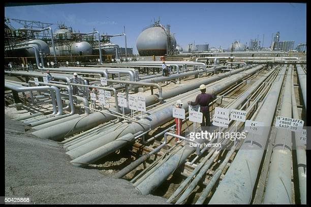Worker dwarfed by sprawling network of pipelines storage tanks at Saudi Aramco oil refinery loading terminal at Ras Tanura Arabia