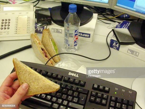 A worker eating at their desk Workers are taking less than half an hour for lunch because of spiralling pressures and one in five have no meal break...