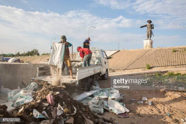 A worker empties out a bag of rubble at a construction site in Vientiane Laos on Thursday Nov 2 2017 Located in the Mekong region Southeast Asia's...