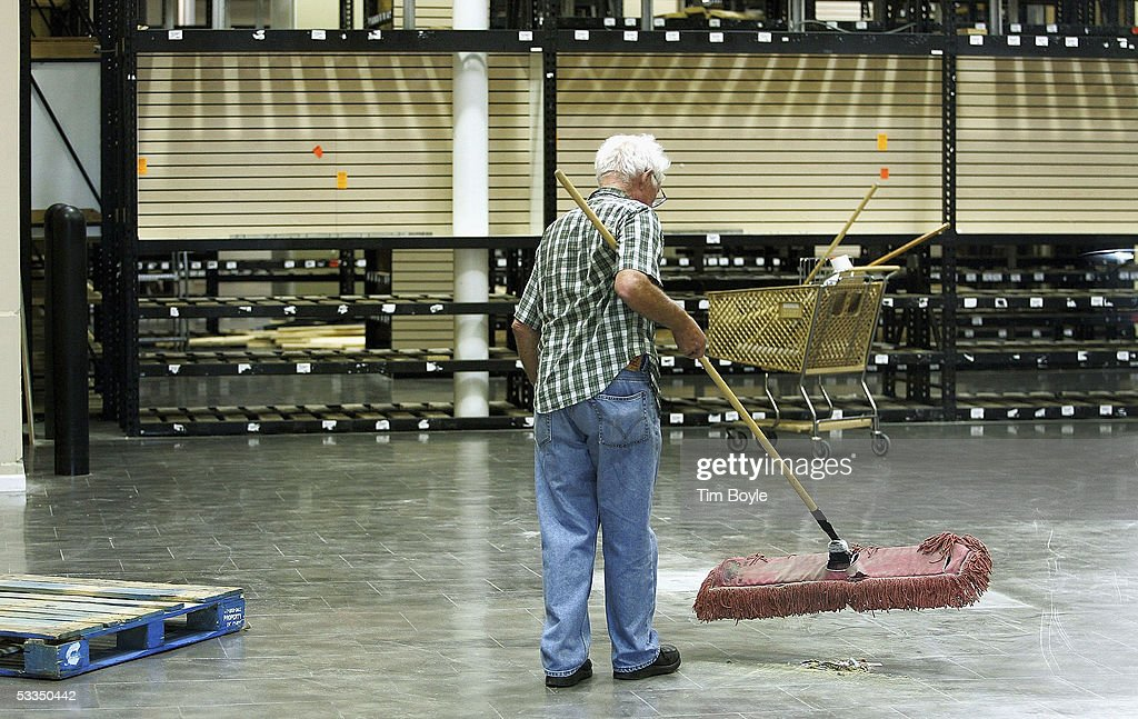 Worker Eugene Doherty is seen through a glass door as he sweeps the floor inside a closed Expo Design Center store August 10, 2005 in Schaumburg, Illinois. Home Depot has said it plans to close a third of its Expo Design Centers in the US, closing three of its five stores in the Chicago area.