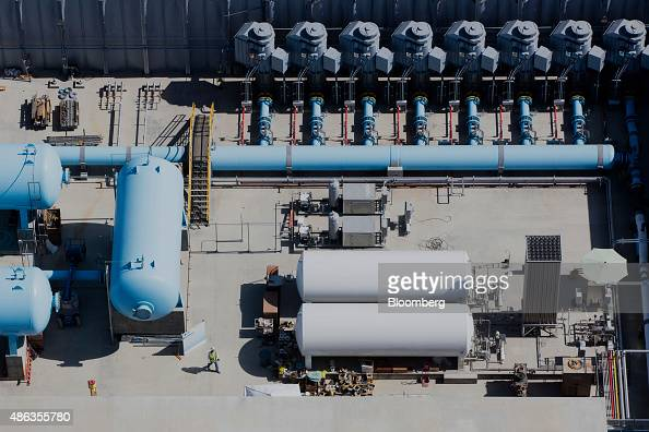 A worker examines machinery at the Carlsbad Desalination plant under construction in this aerial photograph taken over Carlsbad California US on...