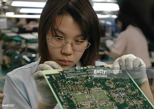 A worker examines soldering points on a circuit board for a mobile phone network base station at Fujitsu Ltd's Nasu Factory in Tochigi Prefecture...