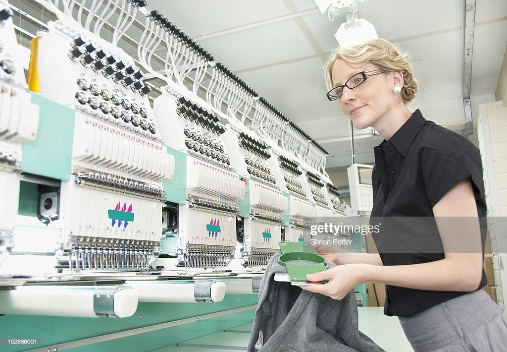 Worker examining fabric in factory : Stock Photo
