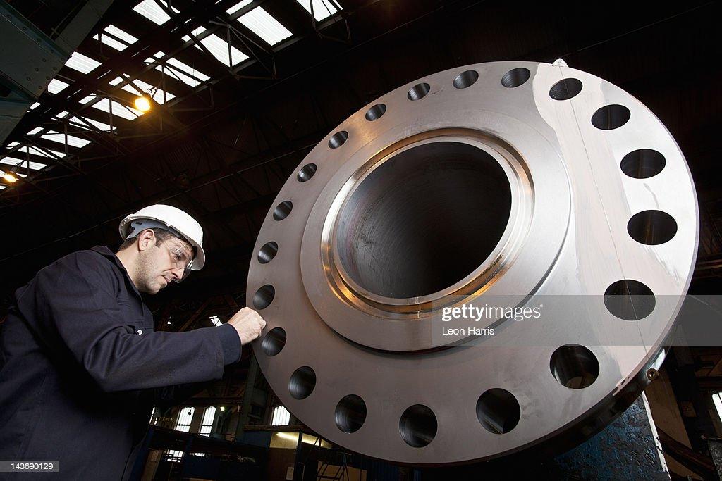 Worker examining metal in steel forge