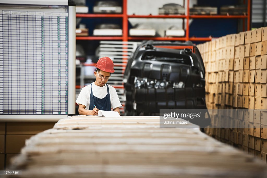 Worker examining product in manufacturing plant : Stock Photo