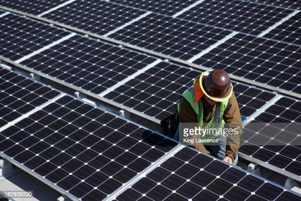 Worker examining solar panels outdoors