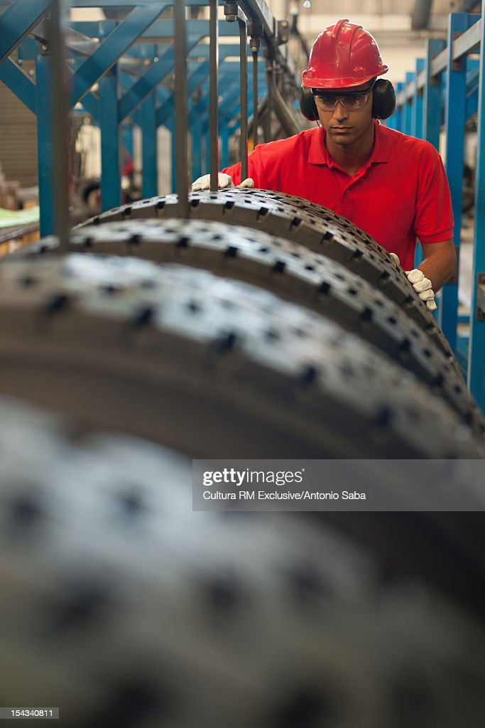 Worker examining tires in factory : Stock Photo