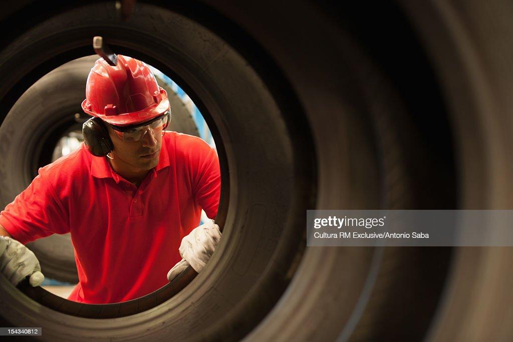 Worker examining tires in factory