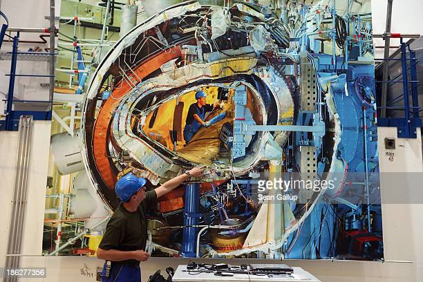 A worker explains a photo taken about a year and a half ago that shows construction of the interior plasma chamber of the Wendelstein 7X experimental...