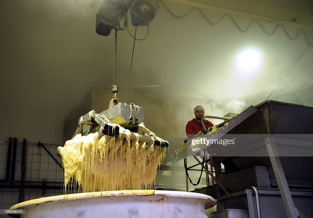 A worker extracts fermented cabbage from tanks in the sauerkraut unit of Charles Christ, a French firm specialized in canned cooked dishes and condiments, on January 11, 2013 at Connerre, western France.