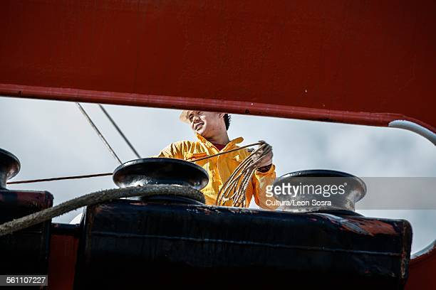 Worker fastening ropes to mooring posts on board oil tanker