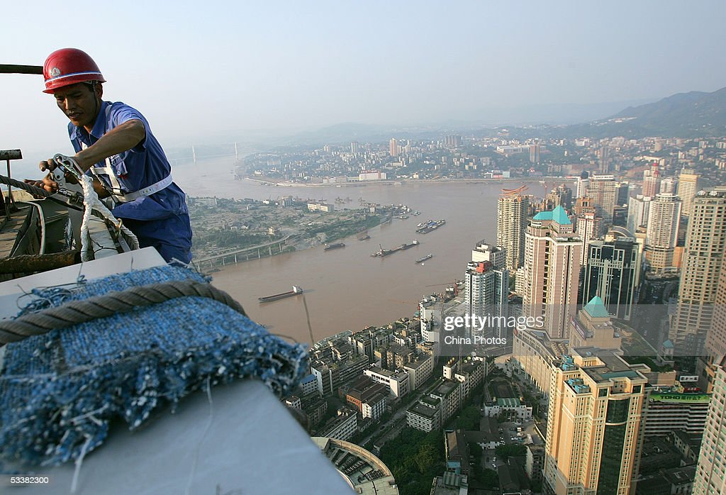 A worker fastens safety ropes on the top of Chongqing World Trade Center before cleaning an external wall of the building on August 11 2005 in...