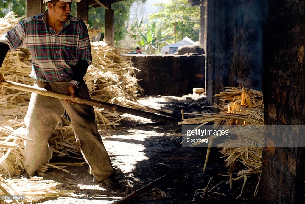 A worker feeds shredded sugar cane into an oven for making handmade panela, a solid piece of unrefined whole cane sugar obtained from the boiling and evaporation of sugarcane juice, at a traditional sugar mill in Tepetitan, El Salvador on Sunday, Feb. 26, 2012. Global sugar supply will be 'under pressure' amid significant demand growth by 2020, which may push prices up further, according to Mannheim, Germany-based refiner Suedzucker AG. Photographer: Juan Carlos/Bloomberg via Getty Images