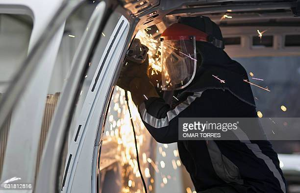 A worker files the edges of a SUV's dismantled chassis to armourplate the vehicle on May 2 2011 at an armor plating company in Mexico City The...