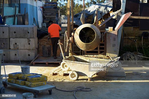 A worker fills a container with sand as a concrete mixer operates at the yard of Gully Concrete supplies in Melbourne Australia on Tuesday Aug 16...