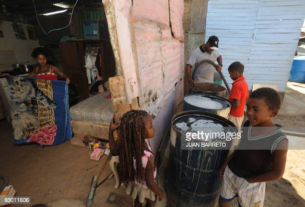 A worker fills a drum with water from a tanker at the Mariche lowincome neighborhood of the Sucre municipality eastern Caracas November 12 2009...