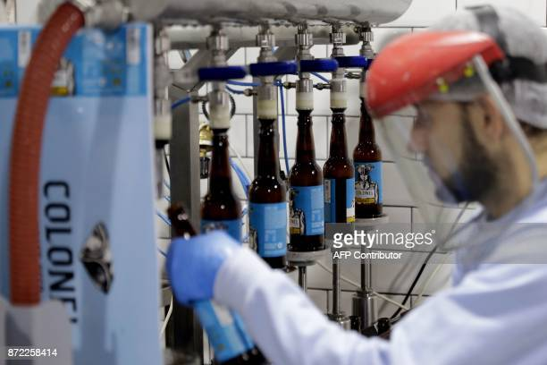 A worker fills beer bottles at the Colonel Beer brewery in the town of Batroun north of Beirut on October 5 2017 For decades beer in Lebanon has...