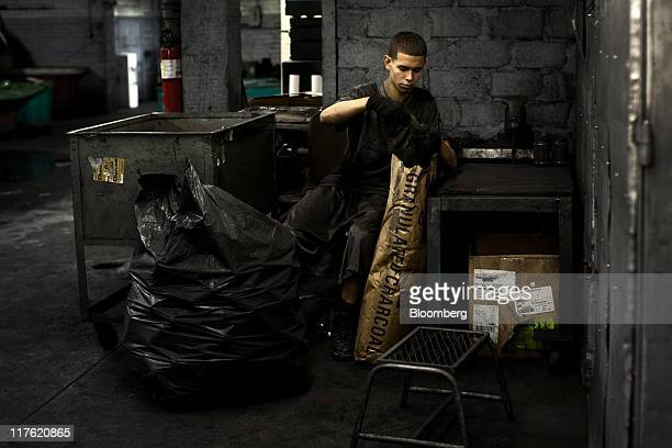 A worker fills containers with charcoal powder used for artists renderings at the General Pencil Co's factory in Jersey City New Jersey US on...