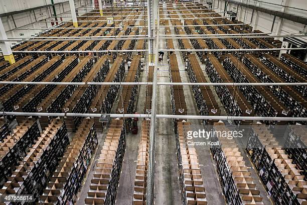 A worker fills inventory among shelves lined with goods at an Amazon warehouse on November 17 2015 in Brieselang Germany Germany is online retailer...