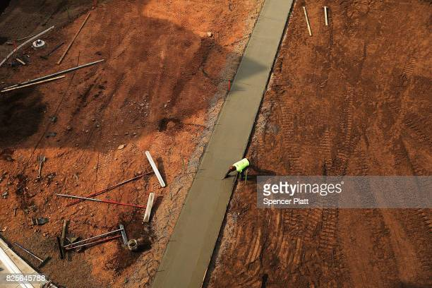 A worker finishes a sidewalk at Canal Crossing a new luxury apartment community consisting of 393 rental units near the university city of New Haven...
