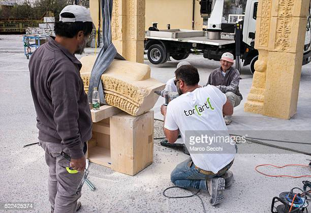 A worker finishes one of the marble blocks which will form part of the 3D replica of Palmyra's Arch of Triumph at the marble caves of Carrara on...