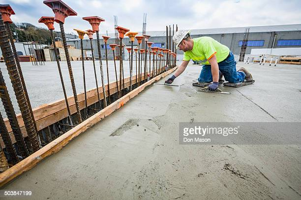 Worker finishing concrete at construction site
